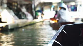 Cruising on paddle boat at Damnoen Saduak Floating Market in Ratchaburi, Thailand. No face and blur atmosphere
