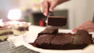 Cutting Chocolate Brownie Cake into slices and set on plate