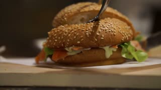 Cutting smoked salmon burger in sesame bun