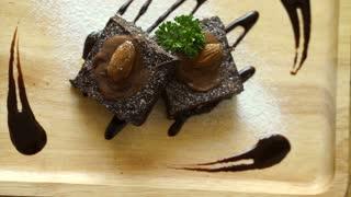 Dark chocolate topping brownie cake. Homemade coffee shop dessert serve on light wood plate
