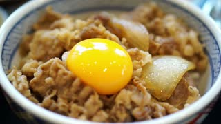 Delicious eating raw egg yolk on food. Japanese beef over rice. Poached runny egg running out