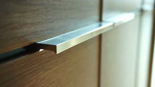 Detail of stainless steel handle at cloth cabinet in condominium, modern furniture