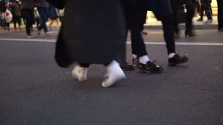 Detail view of feet of Walking people at shopping street in evening