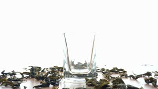 Dried Tea leaf filling in clear glass on white background