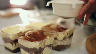 Dusting tiramisu cake by powdered cocoa