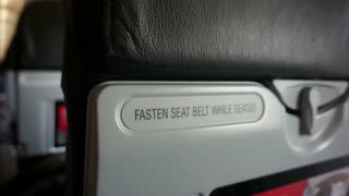 Fasten seat belt while seated and life vest under the seat sign across airplane seating. Abstract safety