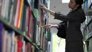 Female, Asian girl student stand searching bookshelves, reading books