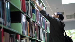 Female, Asian girl student stand searching bookshelves, reading books