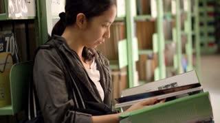 Female, girl student stand beside bookshelves, reading books library