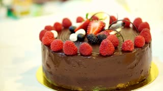 Female hand cutting on pieces the Sticky chocolate cake with fresh strawberries and berries