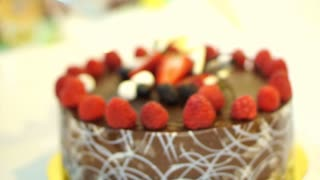Female hands deploy wrapper of Sticky chocolate cake with fresh strawberries and berries