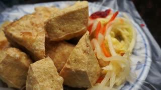 Fried stinky tofu with pickle vegetable and sauce on the side. Serve on plastic over plate