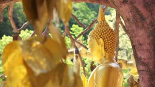 Full HD Sculpture of Gold Buddha sculpture behind layers of gold leaves tree