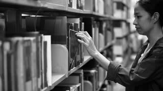 Girl student walking between shelves, searching for books. Video in black and white color
