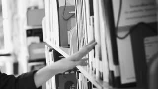 Girl student walking between shelves, searching for books. Video in black and white colors