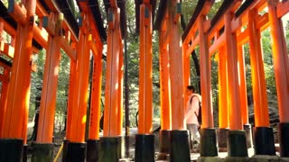 Girl walking in Red gate torii at Fushimi Inari temple shrine in Kyoto, Japan