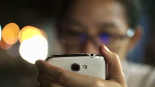 Glassed Asian women texting using smart phone with city at night light background