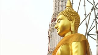 Golden Buddha statue with construction scaffold on the back and pagoda background