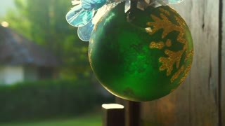 Green Christmas bauble ornament decorations hanging at window morning sun
