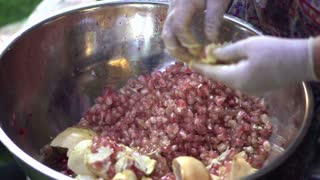 Hand peeling pomegranate seeds to make juice in Asian street food market