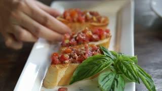 Hands taking yummy bruschetta and fresh basil leaves to eat