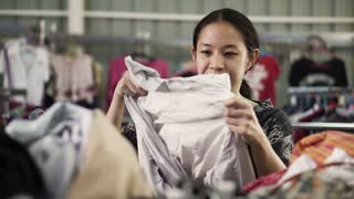 Happy Asian mixed race girl looking for good cheap clothes in sale bazaar