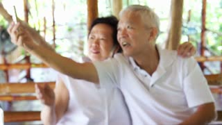 Happy Asian senior couple taking selfie in park on mobile phone