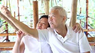 Happy Asian senior couple taking selfie in park on mobile phone