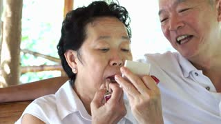 Happy lovely Asian senior couple, woman do make up lipstick and show to her husband. Long lasting love