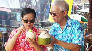 HD video of Asian senior couple travel to thailand floating market. Drinking frsh coconut juice
