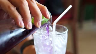 Herb drink, Butterfly pea, Clitoria ternatea L. flower mixed with lime, lemon being poured in to the glass