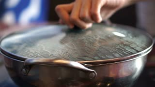 Hot pot, shabu lid cover remove with hand. Steam gushing out from boiled water