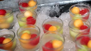 Iced fruits scoop. Cold party summer finger food cocktail with tropical fruits