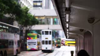 Iconic Hong Kong tram transportation concept. People waiting at the tram station with background of car approaching