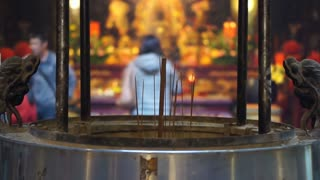 incense pot in front of Buddhist Tao temple in China. blur background people paying respect