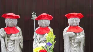 Japanese buddhist stone monk statues wearing red clothes standing in row at temple front