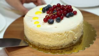 Knife cutting whole pound of cheesecake with berries on top