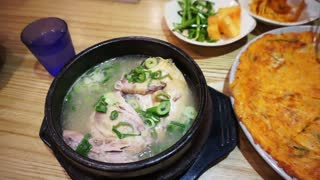 Korean food, kimchi pancake, ginseng chicken soup and variety of side dishes