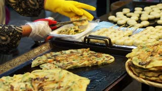 Korean local food, Green onion pancake being cut at street food stall in tourist shopping area