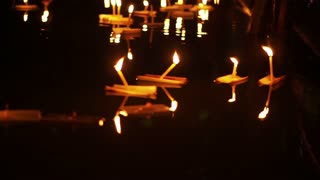 Loi Krathong Festival in Chiangmai, Thailand. Hand releasing floating decorated baskets and candles to pay respect to river goddess. Thai traditional culture on full moon night