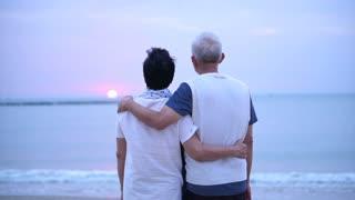 Loving Asian senior couple happy together at ocean sunrise
