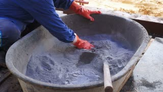 Male worker Mixing cement for Construction. Prepare powder concrete and hand sourcing out