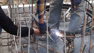 Man welding metal on site at work construction site