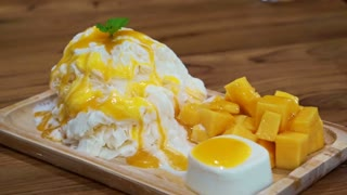 Mango shaved ice with ice cream and custard. Tropical fruit cold sweet