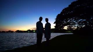 Mature Asian senior couple celebrating anniversary at lake side, morning moon and sunrise