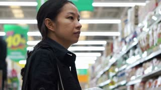 Mixed race Asian mother shopping for stuffs in baby section