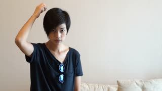 Mixed race hipster Asian girl setting her short hair in front of mirror