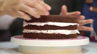 Patisserie chef baking decorating chocolate sponge cake. Putting white cream in the middle layers