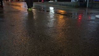 People crossing walking on wet street at night. City life abstract