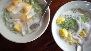 Point of view of hand eating Thai dessert cuisine from top. Coconut milk sweet POV